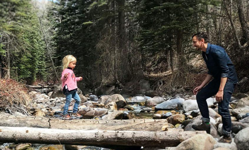 Father and daughter hiking across a log in Vail