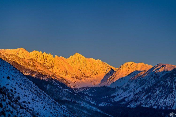 sun setting on snowy mountain peaks from 99 Vail Road